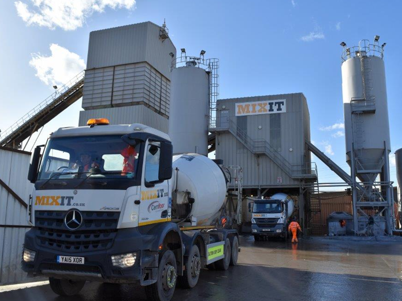 Mixit branded concrete mixer truck on site with large concrete silos with Mixit branded on them
